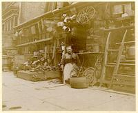 Unidentified woman posed in front of a shop, New York City, undated [c. 1893-1902].