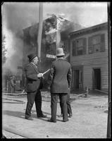 Bystanders talking to a police officer near a burning building, Bronx, N.Y., undated [c.1897-1918].