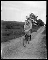 Grace on a bicycle with Will, Garrison, N.Y., 1902.