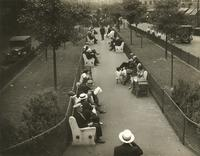 People seated on benches in median strip of Allen Street, New York City.