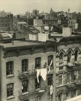Rooftop view of tenement houses with woman hanging laundry, New York City.