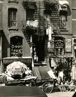 Storefronts, peddlers, and pedestrians on unidentified street, New York City.