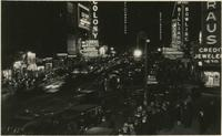 Crowds, traffic, and illuminated signs at night, Broadway and 52nd Street, New York City.