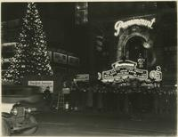 Crowd beside Christmas tree outside the Paramount Theater at night, 1501 Broadway, New York City.