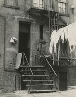 Rear entrance of tenement building with laundry on a clothes line, New York City.