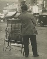 Man with folded cot on unidentified street, New York City.