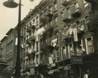 Tenement buildings, pedestrians, and storefronts on unidentified street, New York City.