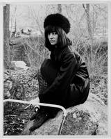 [Woman in a fur cap sitting on a rock with a baby stroller in front of her, holding a baby bottle in one hand and a cigarette in the other, Central Park, New York City, March 26, 1967].