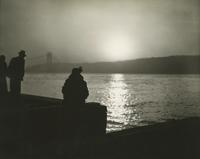 Unidentified people looking across the Hudson River from Manhattan toward the George Washington Bridge at sunset.