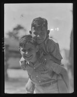 Boy giving a piggyback ride to another camper at William Carey Camp, Jamesport, New York.