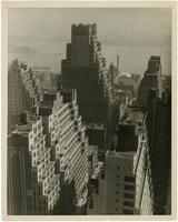 """Rooftops of New York"" [aerial view of buildings and East River from 45th Street between Second and Third Avenues, New York City.]"