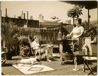 """Fit for a queen is this setting atop private residence in Washington Square, New York"" [Women and dog on rooftop deck of Arthur Shettle residence]."