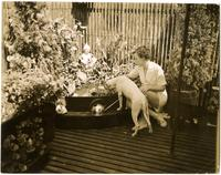 Emily Shettle and dogs at fishpond on rooftop deck, Arthur Shettle residence, Washington Mews, New York City.