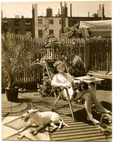 """Comfort of a queen atop private dwelling in New York City"" [Woman and dogs, Arthur Shettle residence, Washington Mews]."