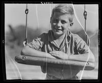 Boy leaning on a swing at William Carey Camp, Jamesport, New York.