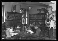 """Angelo"" and other boys reading in the library at Tompkins Square Building [i.e. Harriman Clubhouse], Lower East Side, New York City."