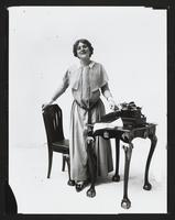 "Edna May as secretary with typewriter, ""school girl 6,"" undated [circa 1900-1910]."