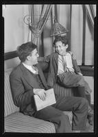 """Angelo"" sitting with instructor on couch at Tompkins Square Building [i.e. Harriman Clubhouse], Lower East Side, New York City."