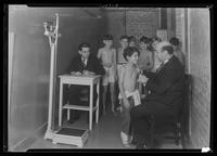 """Angelo"" receiving medical examination at Tompkins Square Building [i.e. Harriman Clubhouse], Lower East Side, New York City."
