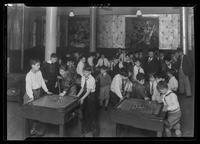 """Angelo"" with large group of boys playing carrom in game room at Tompkins Square Building [i.e. Harriman Clubhouse], Lower East Side, New York City."