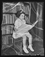 """Miss Boys' Club"" seated with a book in front of a bookshelf at Tompkins Square Building [i.e. Harriman Clubhouse], Lower East Side, New York City."