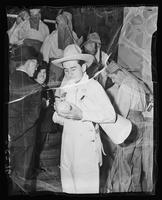 Lowell Thomas in Nine Old Men costume signing a softball at Madison Square Garden (1925-1968), Midtown Manhattan, New York City.