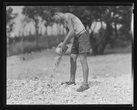 Boy pouring pebbles onto the ground at William Carey Camp, Jamesport, New York.