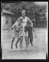 Camp leader Humphrey Ambler carrying two boys under his arms at William Carey Camp, Jamesport, New York.