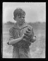Boy wearing a baseball glove at William Carey Camp, Jamesport, New York.
