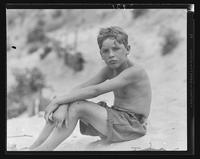 Boy sitting on the beach at William Carey Camp, Jamesport, New York.