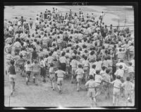 Large group of boys running, backs to the camera, at William Carey Camp, Jamesport, New York.