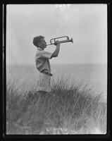 Boy playing bugle on bluff above the Long Island Sound at Willliam Carey Camp, Jamesport, New York.