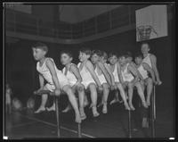 Group of young boys with instructor on the parallel bars.