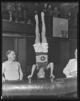 Boy performing a headstand on the pommel horse.