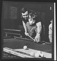 Boy with instructor playing pool.