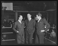 Three unidentified men in boxing ring.