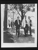 Teenage boys walking on an unidentified campus.