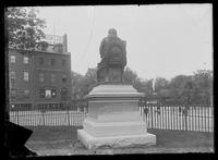 Rear view of the statue of Abraham de Peyster in Bowling Green, with a steam engine visible on an elevated track in the background, New York City, undated (ca. 1895).