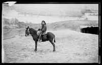 Young Native American girl on a donkey, before the painted backdrop of Buffalo Bill's Wild West Show, Brooklyn, New York City, undated (ca. 1894-1896).