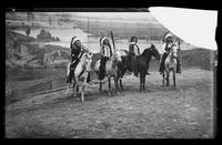 Four unidentified Native American men on horses before the painted backdrop of Buffalo Bill's Wild West Show, Brooklyn, New York City, undated (ca. 1894-1896).